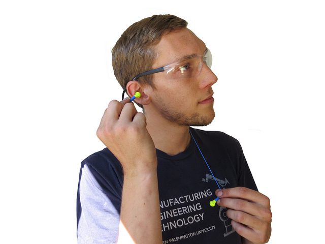 Man inserting earbuds into his ear
