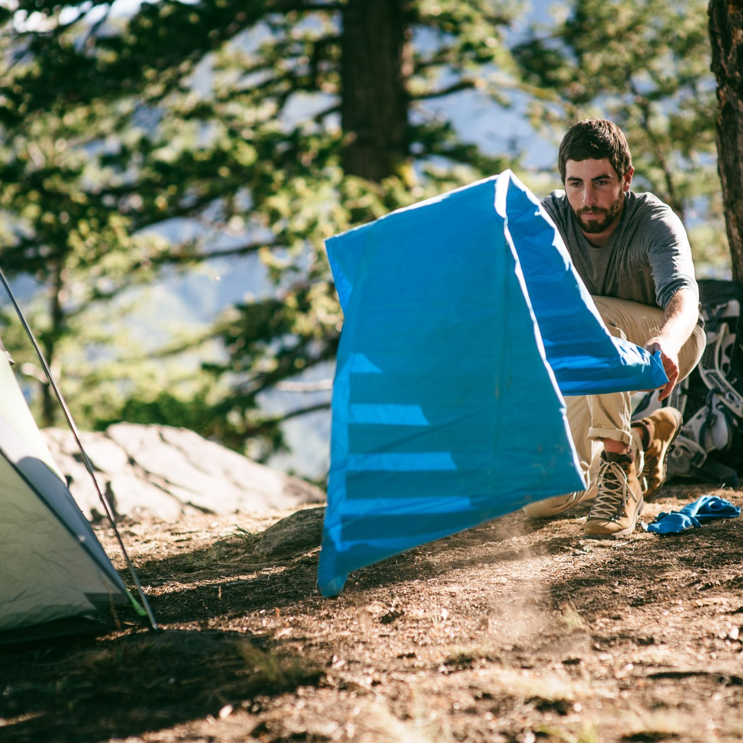 man unrolling a sleeping pad for camping